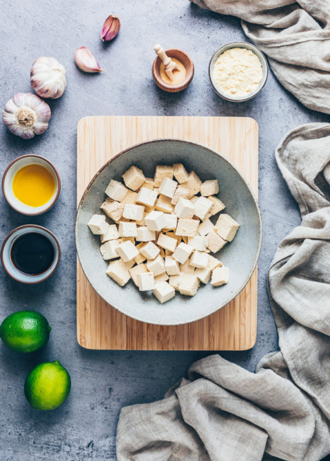 This image shows some plain white unseasoned tofu, cut into cubes and placed in a bowl in the centre of the frame. Around the wooden chopping board on which the bowl is placed are an assortment of ingredients that can be used to flavour the tofu; including limes, whole garlic bulbs, soy sauce and salt and pepper.