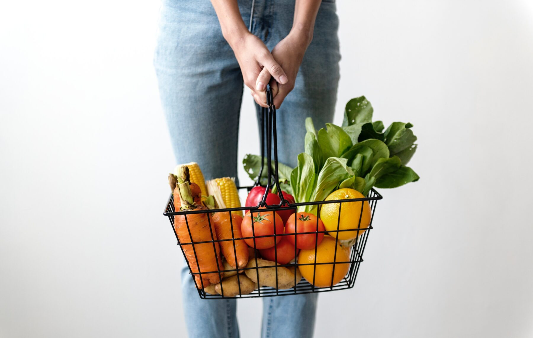 This image shows a shot of a person holding a wire basket in front of themselves. The basket has a mixture of vegetables loaded up inside. The person is wearing skinny jeans.