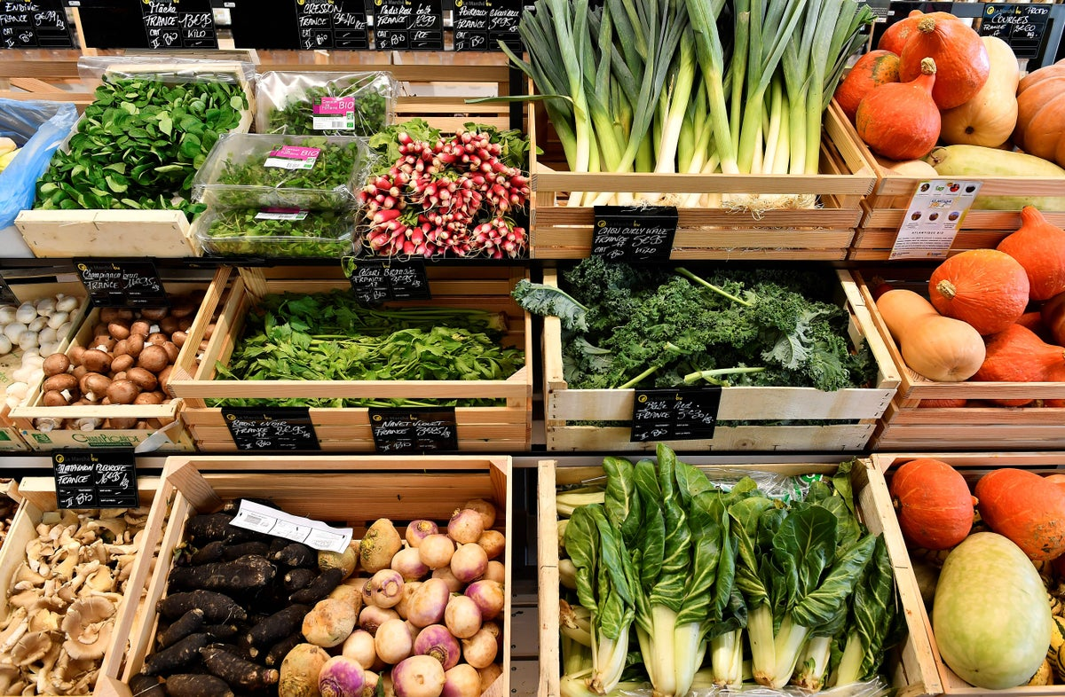 This image shows rows of wooden crates at a market stall or food produce shop, all separately filled with different vegetables.